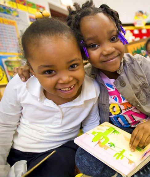 two young students link arms while smiling and reading a book   Reading in Motion