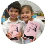 two students in a pre-k reading program hold up books and smile | Reading in Motion